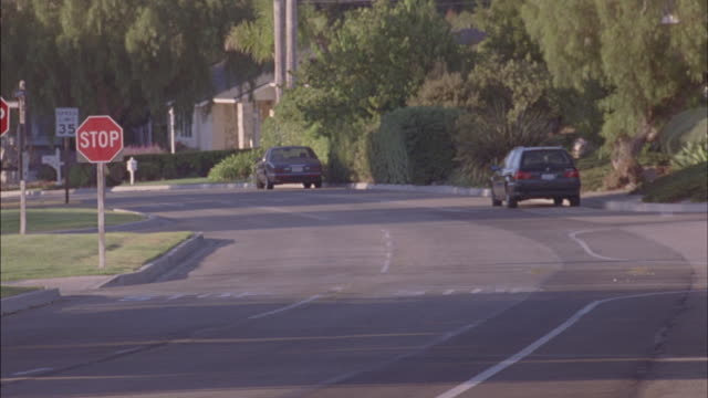 A car runs the stop sign which causes a car to swerve to avoid an accident.