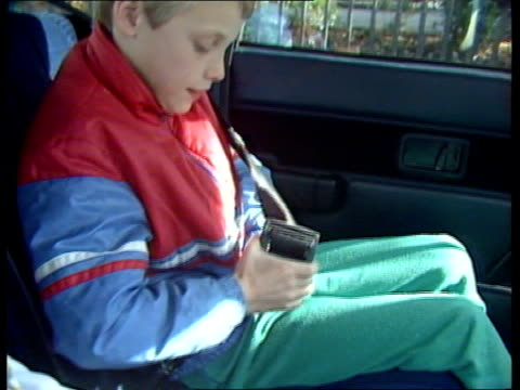 stockvideo's en b-roll-footage met child seatbelts **** rushes kept / rushes not kept ** england london side young boy belting up in back seat of car cms side young girl ditto as boy... - veiligheidsgordel