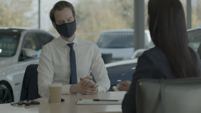 car sales man dealer in auto showroom wearing face mask and customer signing contract and handing over key - shirt and tie stock videos & royalty-free footage