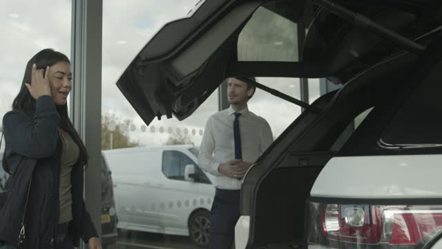 car sales man showing customer car in automotive dealership showroom - shirt and tie stock videos & royalty-free footage