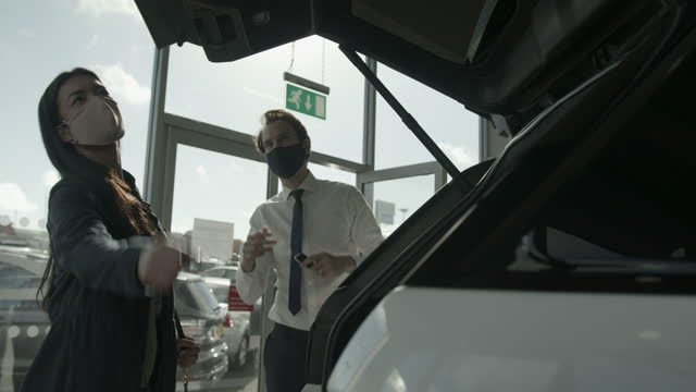 car sales man wearing protective face mask showing customer car in automotive dealership showroom - shirt and tie stock videos & royalty-free footage