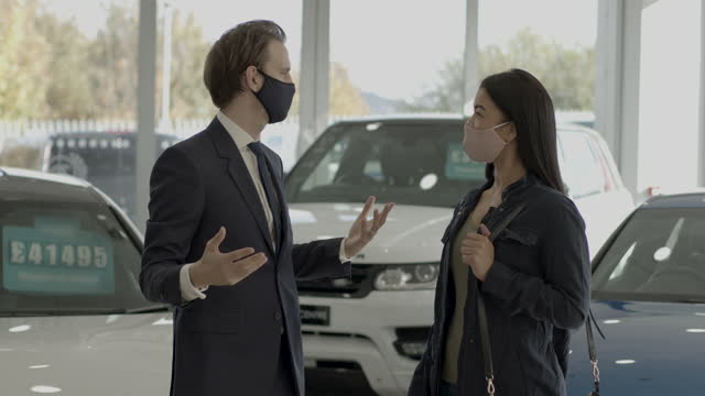 vídeos de stock e filmes b-roll de car sales person talking to customer wearing protective face mask in car dealership showroom - aluguer de automóveis
