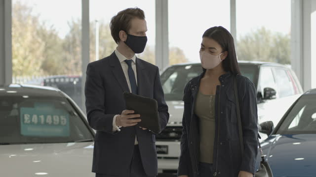 car sales person talking to customer wearing protective face mask in car dealership showroom and looking at digital tablet - formal businesswear stock videos & royalty-free footage