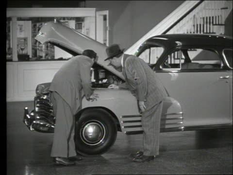 vidéos et rushes de b/w 1948 car salesman shows car engine to man in showroom / chevrolet - chevrolet