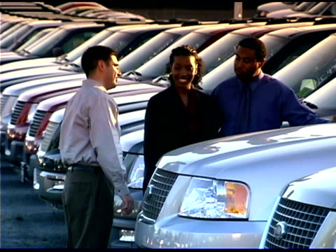 a car salesman shows suvs to a couple on the car lot. - selling stock videos and b-roll footage