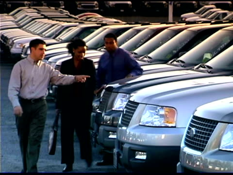 A car salesman shows suvs to a couple on the car lot.