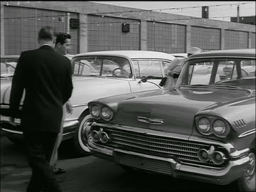b/w 1958 car salesman talking to couple + showing them chevrolet delray in lot - 1958 stock videos & royalty-free footage