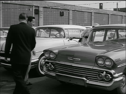 vídeos de stock e filmes b-roll de b/w 1958 car salesman talking to couple + showing them chevrolet delray in lot - stand de carros