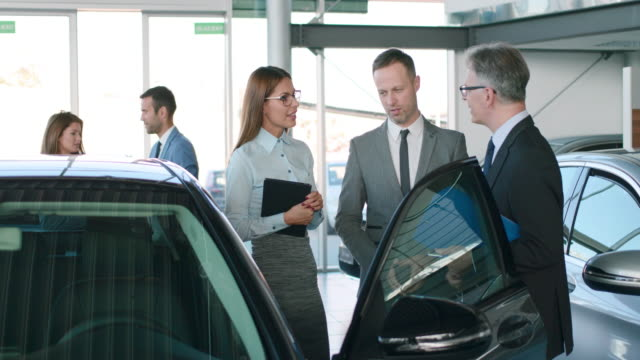 car salespersons discussing business strategy at car dealership - well dressed stock videos & royalty-free footage