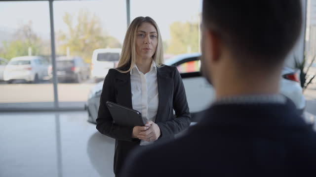 car saleswoman talking with male customer in car dealership - sale stock videos & royalty-free footage
