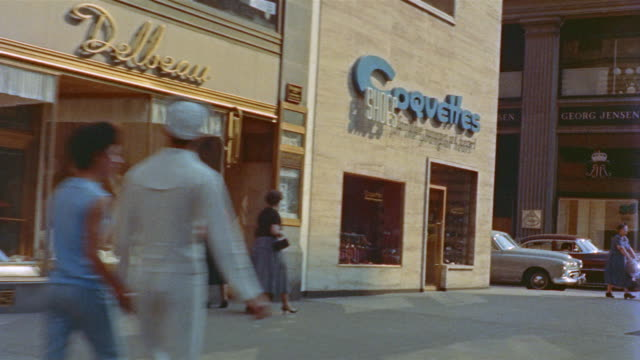 1956 Car POV of shoppers and stores up Fifth Avenue from 53rd Street to 55th Street / New York City