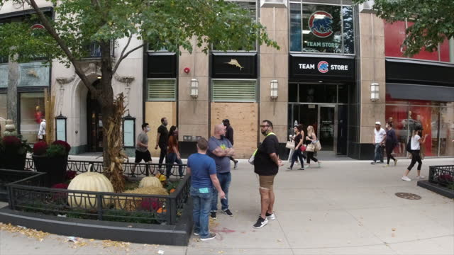 car side view of people wearing protective face mask walk and shop in chicago amid the 2020 global coronavirus pandemic. - loft apartment stock videos & royalty-free footage