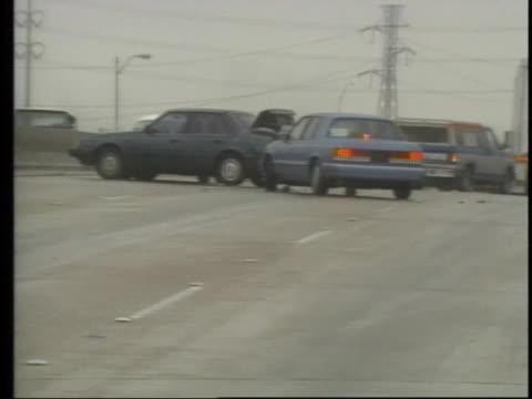 vídeos de stock e filmes b-roll de a car skids into stalled traffic on an icy road - condição