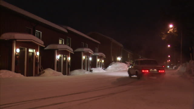 a car skids on a snow covered road outside a house in the winter sweden. - 横滑り点の映像素材/bロール