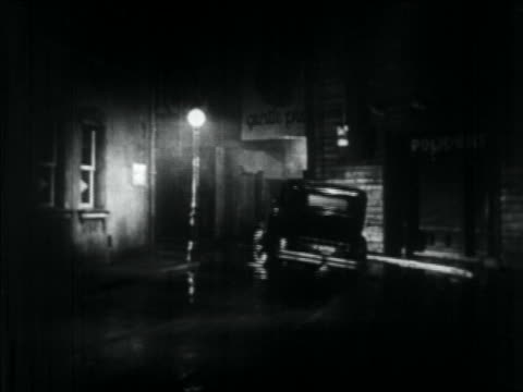 b/w 1934 rear view car speeding away around wet street corner at night - criminal stock videos & royalty-free footage