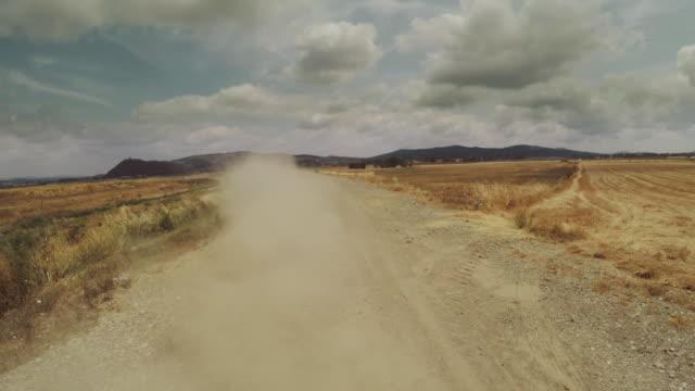 vídeos de stock, filmes e b-roll de carro acelerando offroad no estado selvagem: vista de estrada de terra e poeira traseira - estrada em terra batida