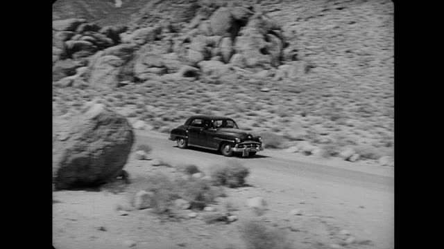 1953 a car speeds down a desert road - film noir style stock videos & royalty-free footage