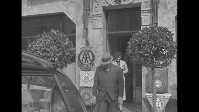 car stands outside door of grand hotel vendome in paris as spectators stand nearby / wallis simpson exits hotel with woman they get into car / car... - wallis simpson stock videos & royalty-free footage