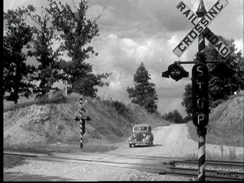 1935 ws car stops at railroad crossing as train speeds past - 1935 stock videos & royalty-free footage