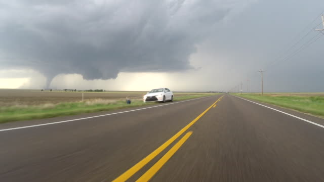 car pov of storm chasers driving down route 283 past other chasers parked along the side of the road as a large tornado tears up a kansas wheatfield... - kansas city kansas bildbanksvideor och videomaterial från bakom kulisserna