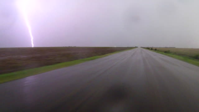car pov of storm chasers driving near kinsley ks as vivid cloud to ground lightning bolts shoot out of a supercell thunderstorm and strike the ground... - lightning strike stock videos and b-roll footage