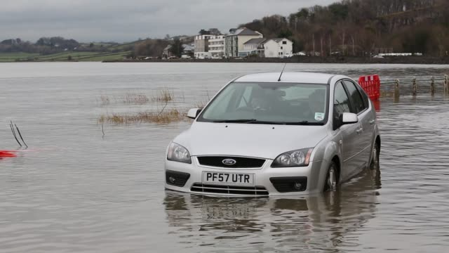 car stranded in flood waters on the road at storth on the kent estuary in cumbria, uk, during the january 2014 storm surge and high tides. - power in nature stock videos & royalty-free footage