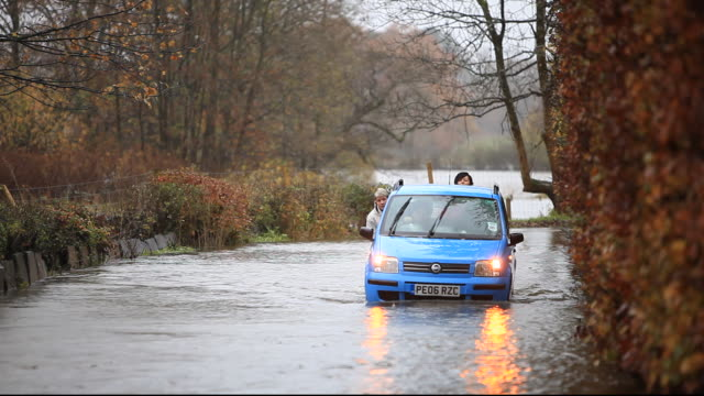 a car stuck in flood water during torrentail rain in ambleside, lake district, cumbria, uk. - weather stock videos & royalty-free footage