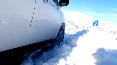 car stuck in winter, spraying snow over camera - slippery stock videos & royalty-free footage