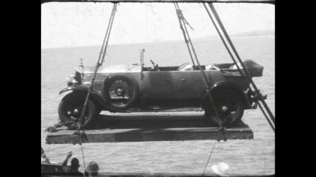 car swings over side of ship on platform boats from shore lined up along the ship - colonial stock videos & royalty-free footage