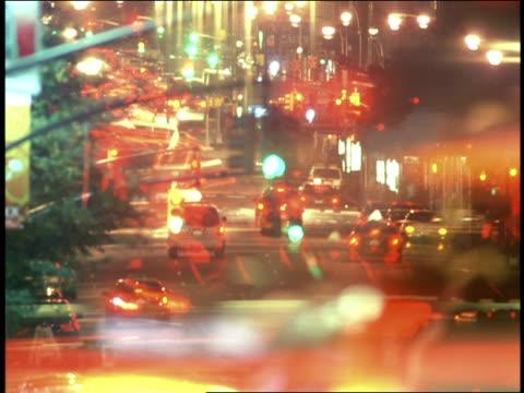 Car taillights streak down a New York City street at night.