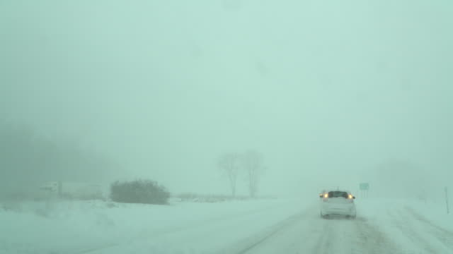 the road is barely visible as heavy snow and strong winds create whiteout conditions during an extreme lake effect snow event near pulaski ny - loch stock videos & royalty-free footage