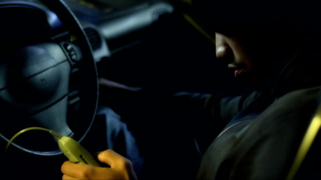 Car thief sitting in the car decoding it with decoder