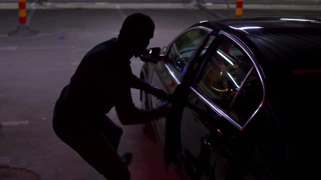 vidéos et rushes de voleur de voiture essayant d'ouvrir la porte de voiture avec le lockpicker - partie de véhicule