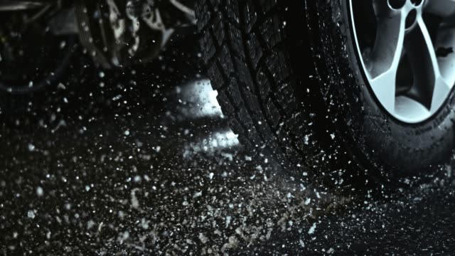 SLO MO Car tire rotating in place causing water to splash into the air