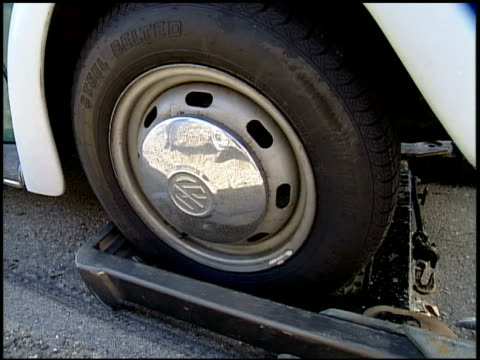 a car tire settles into a towing bracket. - rimorchiare video stock e b–roll
