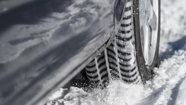 どこにも、雪の中で立ち往生している車のタイヤは場所で回転 - 横滑り点の映像素材/bロール