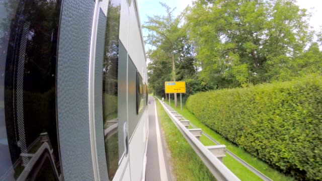 pov: car towing a caravan on bavarian road in countryside - tunnel stock videos & royalty-free footage