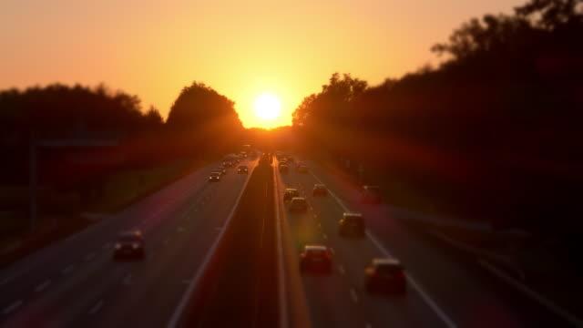 Pkw-Verkehr auf der Autobahn bei Sonnenuntergang