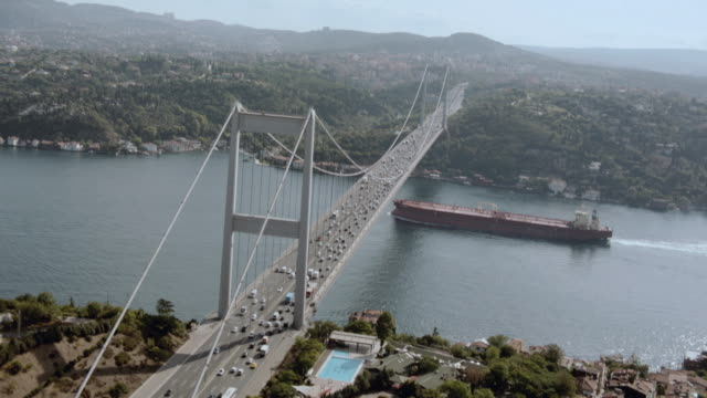 aerial car traffic traveling along the bosphorous bridge while a cargo ship is cruising underneath / istanbul, turkey - july 15 martyrs' bridge stock videos & royalty-free footage