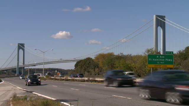 car travel on the belt parkway in brooklyn the span of the verrazano-narrows bridge is behind and a sign for 4th ave and ft hamilton pky - hamilton new york state stock videos & royalty-free footage
