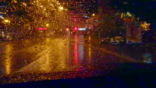 Car Travel on the City Road at Night When it Raining and Using Windshield Wiper