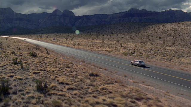 AERIAL WS TS Car Traveling Fast Along Two Lane Desert Road