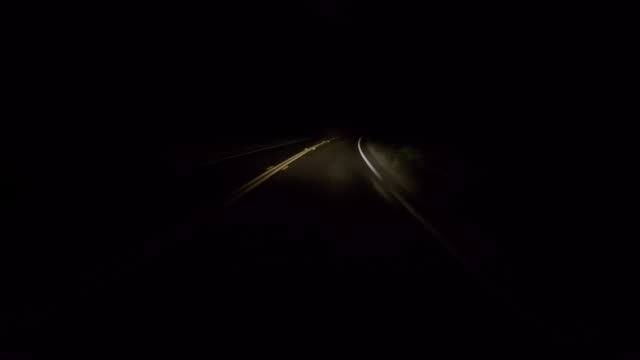 A car traveling on a rural road at night with the headlights on.