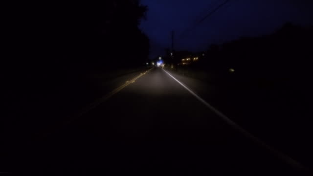 a car traveling on a rural road at night with the headlights on. - small town stock videos & royalty-free footage
