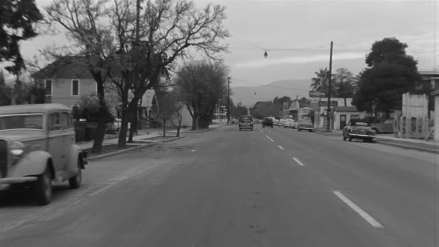 1955 b/w montage pov car travelling down suburban streets / el monte, california - bewegliches hintergrundbild stock-videos und b-roll-filmmaterial