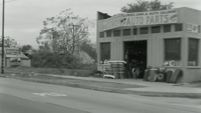 1955 b/w pov car travelling through lower class suburb / el monte, california  - anno 1955 video stock e b–roll