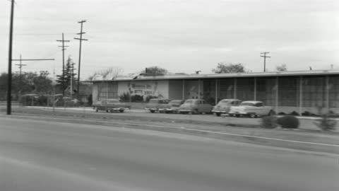 1955 b/w pov car travelling through lower class suburb / el monte, california  - moving process plate stock videos & royalty-free footage