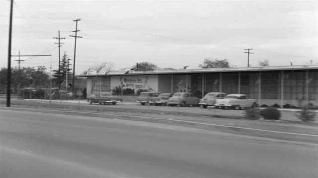 1955 b/w pov car travelling through lower class suburb / el monte, california  - bewegliches hintergrundbild stock-videos und b-roll-filmmaterial