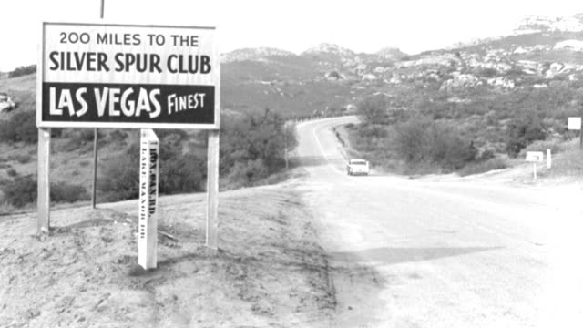"""a car travels down a mountain highway past a road sign that reads """"200 miles to the silver spur las vegas finest."""" - 1958 stock videos & royalty-free footage"""
