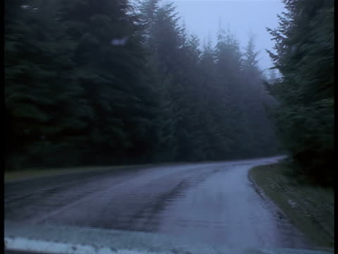 A car travels down a narrow, rainy country road and an oncoming vehicle swerves to avoid a collision.